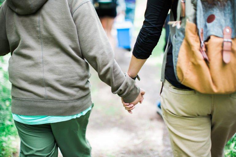 två personer promenerar hand i hand
