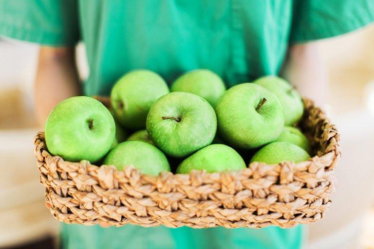 gröna äpplen i en korg