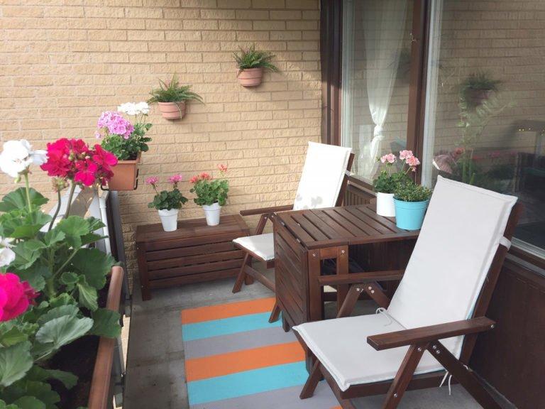 Längan balkong med blommor, stolar och matta