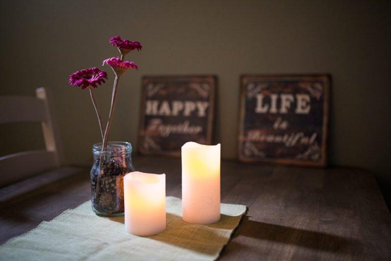 tända ljus och blomma på bord